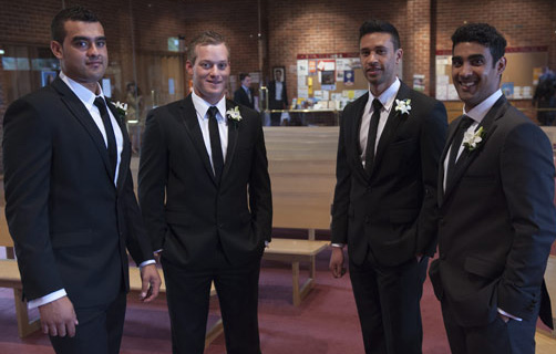 nervous groom and groomsmen wait in church for the bride