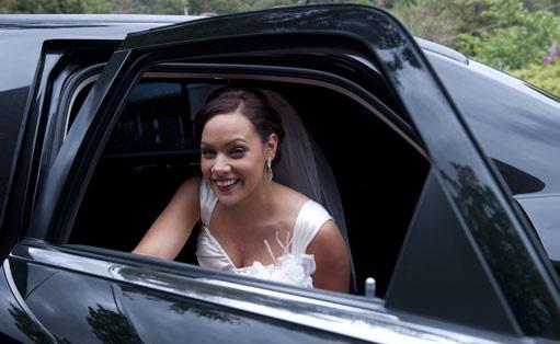 black Chrysler wedding limousine and bride