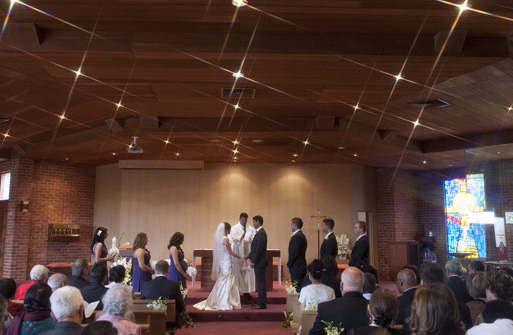 wedding photography showing vows being exchanged, view from back of church