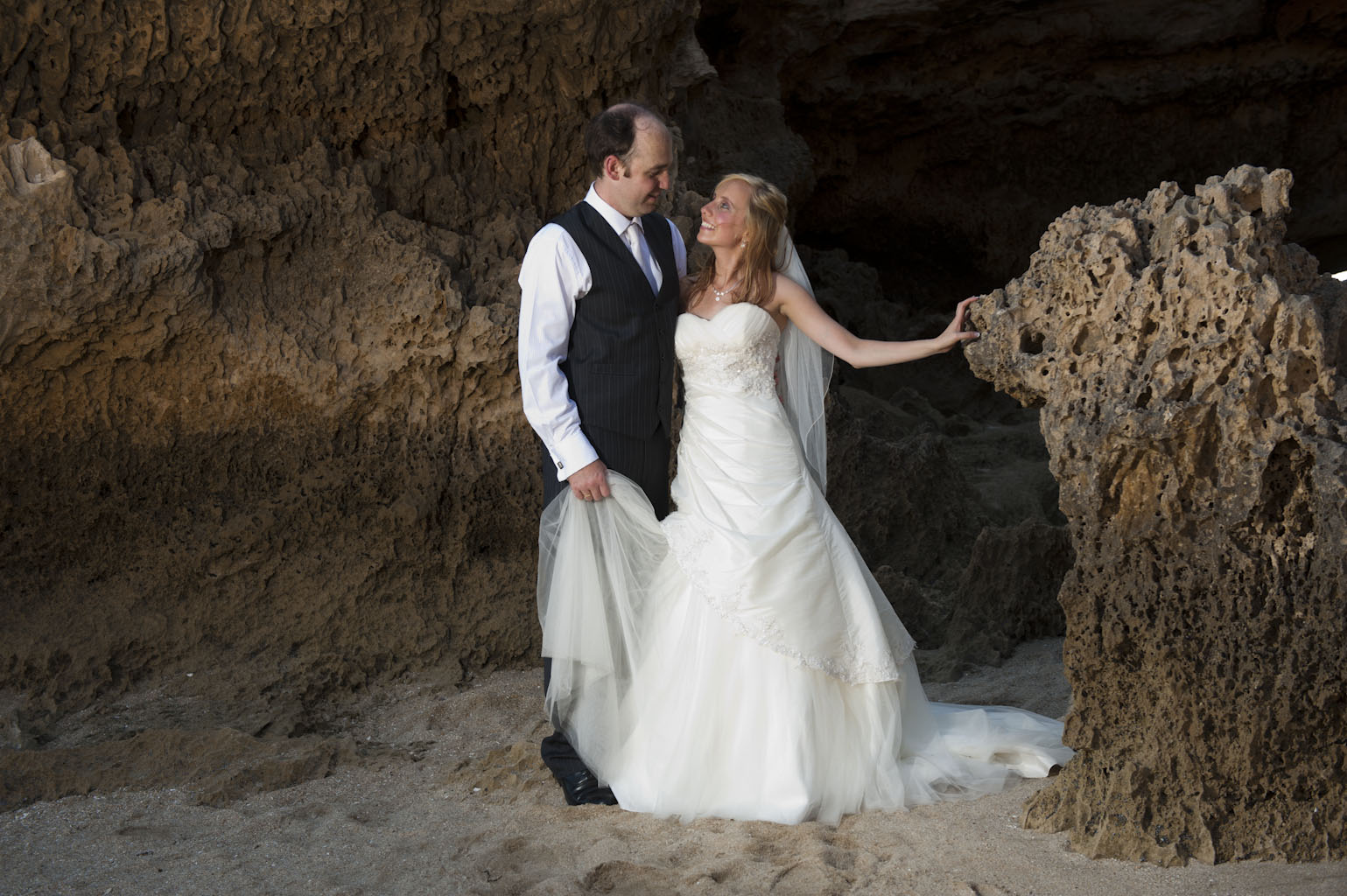 bridal couple stand among beach cliffs