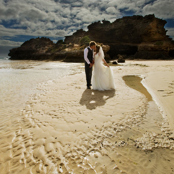 bridal couple framed by rippled sand and water