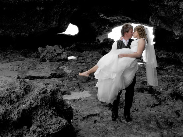 part black and white photo of groom carrying bride on the beach