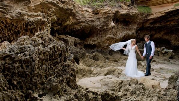 bridal couple walk among beach sand stone outcrops