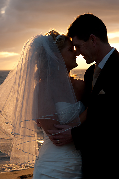 newlyweds silhouetted against beach sunset