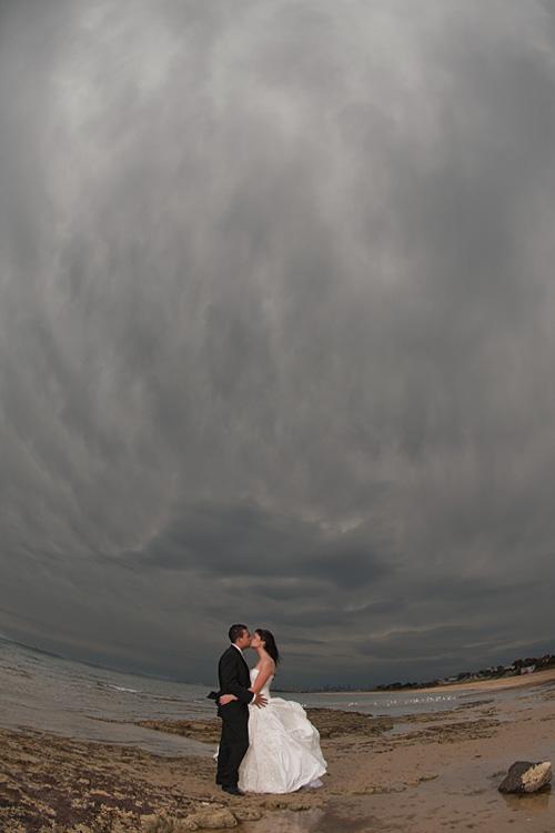 seaside tornado looms above newlyweds blissfully kissing