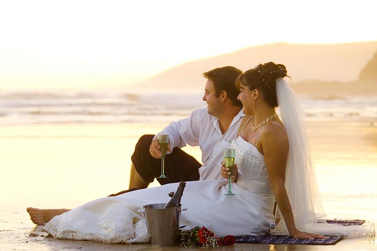 wedding photo of couple enjoying sunset champagne on beach
