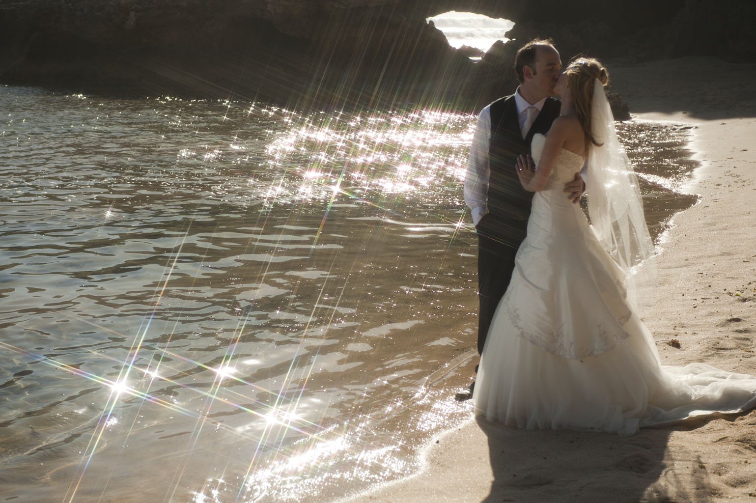 beach wedding photo with sun sparkles on water