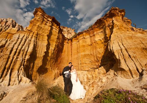 wedding photo of couple against ocean cliff
