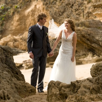 portrait of wedding couple among ocean beach sandstone