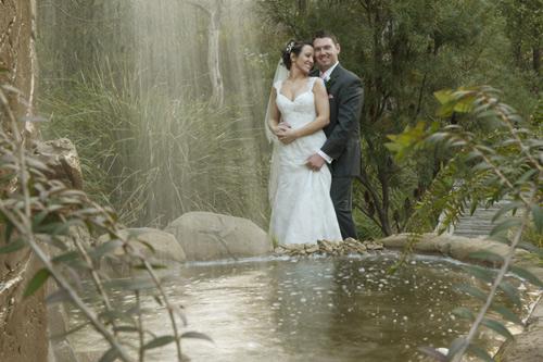 bridal couple embracing behind garden waterfall