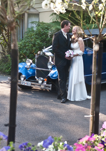hot rod from blue moon rods parked in garden behind wedding couple