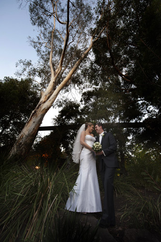 a sweeping tree forms a dramatic compopsition in this garden wedding photo