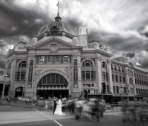 Melbourne bride and Groom outside Flinders Street Station with the traffic and pedestrians in view.
