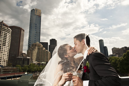 Wedding Photography city Melbourne- a bride and groom on Princes bridge with the background